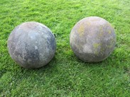 Showning the lichen and weathering of the large pair of antique hand carved stone balls