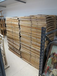 Showing the antique folding slatted chairs stacked safely in our warehouse