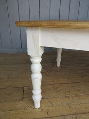 Showing the turned farmhouse legs of the reclaimed plank top table