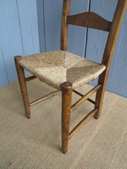 Showing close up of the rush seat of the antique kitchen church chairs