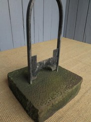 Close up of the base of the wrought iron boot scraper on stone base
