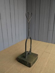 Side view of the wrought iron boot scraper on stone base