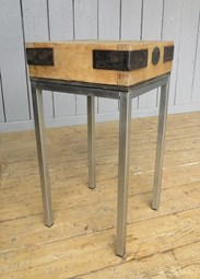 Showing the side of the antique butchers chopping block on stainless steel base