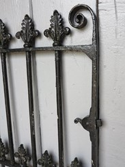 Close up of iron scroll fleur de lis and original latch of the Victorian wrought iron gate
