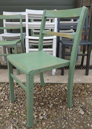 Close up of a stacker chair in hand painted green