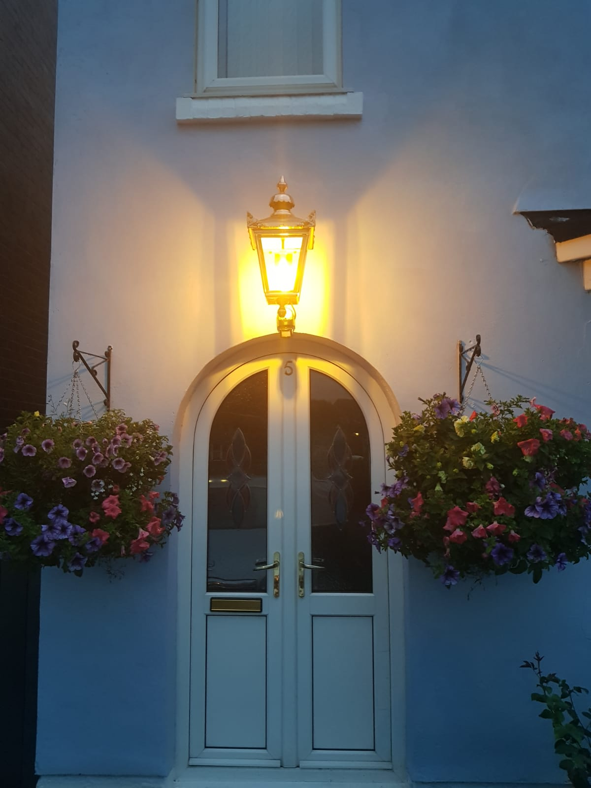 Copper garden lanterns fitted at night in a happy customers home. Traditional Victorian style lanterns at night