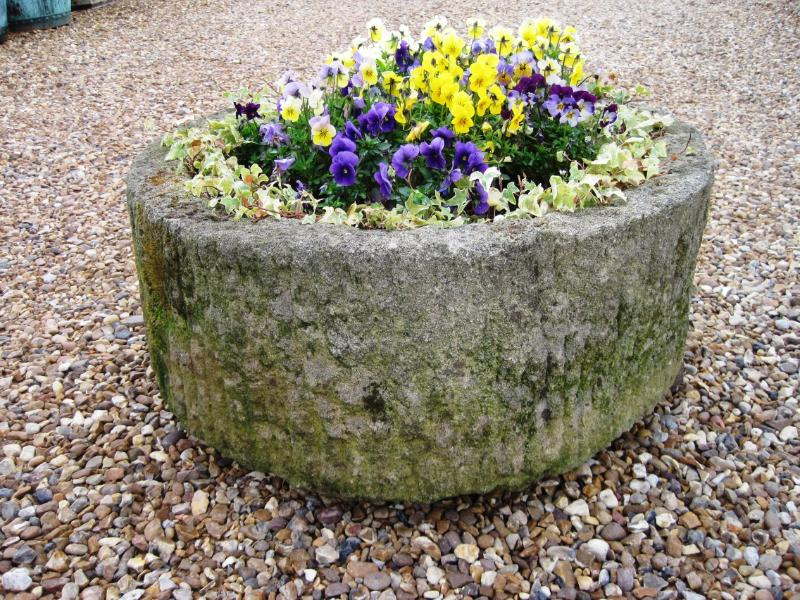 Old salvaged original round stone troughs used as a planter with flowers available to view in our warehouse
