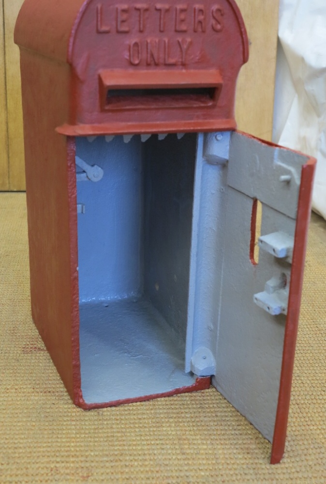 Inside of an original reclaimed Royal Mail Edward the seventh post box, painted in red oxide primer and a red undercoat showing cage and original lock.